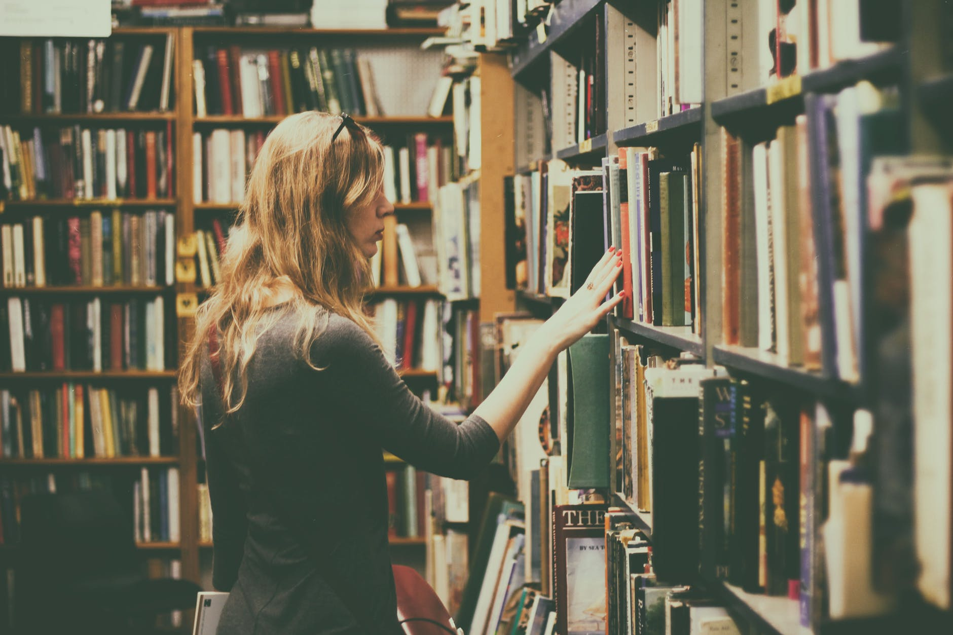 A woman looking over shelves in a book store